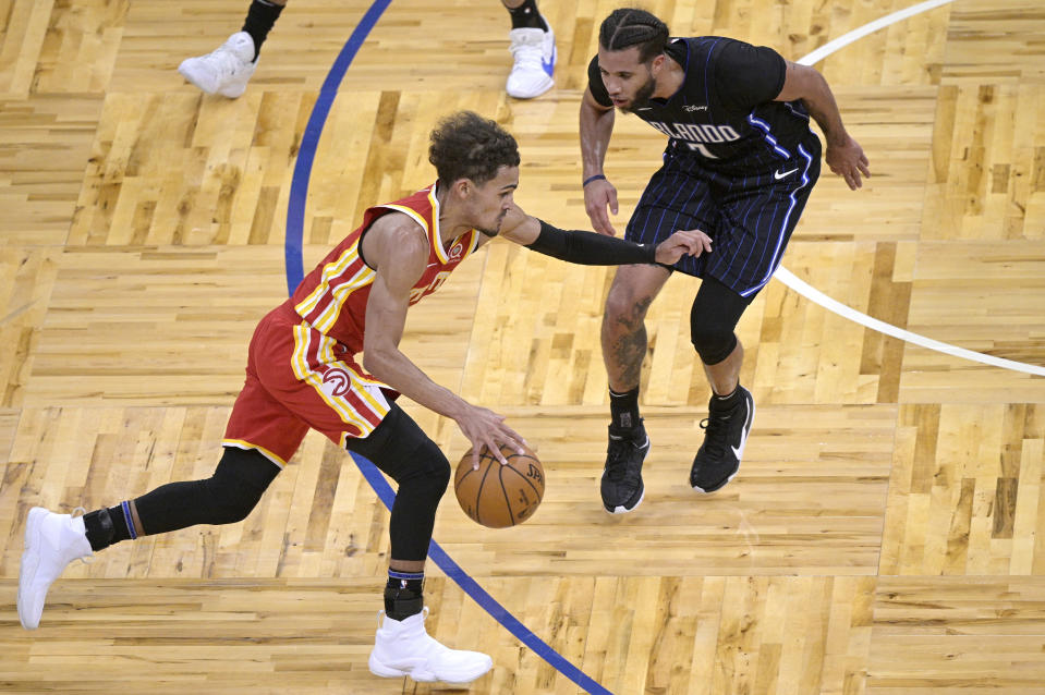 Atlanta Hawks guard Trae Young, left, drives to the basket in front of Orlando Magic guard Michael Carter-Williams (7) during the first half of an NBA basketball game Wednesday, March 3, 2021, in Orlando, Fla. (AP Photo/Phelan M. Ebenhack)
