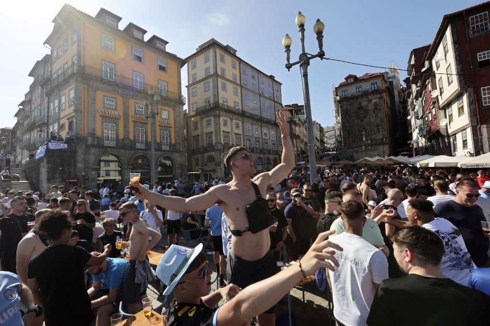 FILE - In this Friday, May 28, 2021, file photo, Manchester City supporters drink and chant by the Douro river bank in Porto, Portugal. English clubs Manchester City and Chelsea will play the Champions League soccer final in Porto on Saturday. (AP Photo/Luis Vieira, File)
