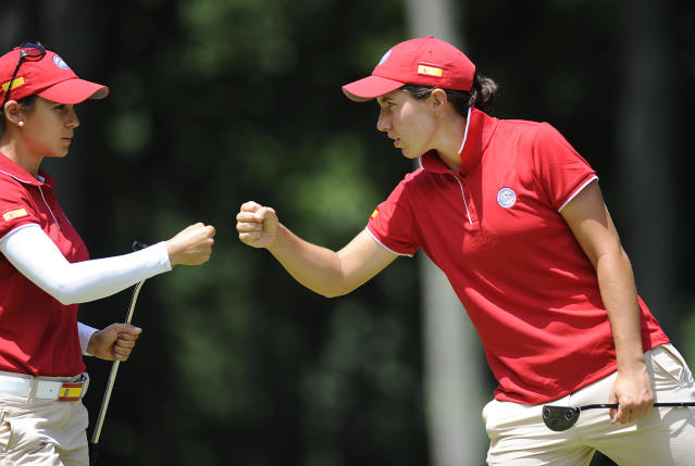 Carlota Ciganda and Azahara Munoz, both of Spain fist pump after completing the first hole during the third round of the International Crown golf tournament on Saturday, July 26, 2014, in Owings Mills, Md.(AP Photo/Gail Burton)