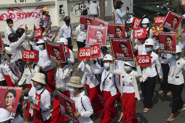 """Students display images of deposed Myanmar leader Aung San Suu Kyi during a street march in Mandalay, Myanmar, Friday, Feb. 26, 2021. In the country's second-largest city, anti-coup protesters took to the streets Friday. By midday, security forces had blocked the main road in downtown Mandalay to prevent the protesters from gathering. A writing on wall, left background, reads """"No Military Dictator."""" (AP Photo)"""