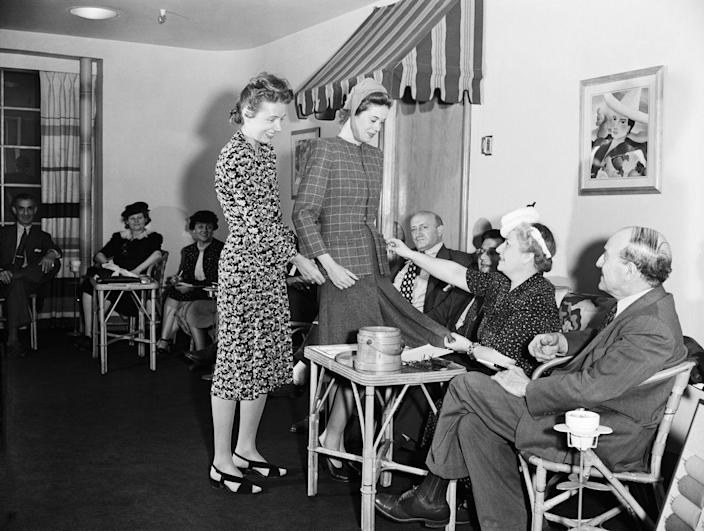 <p>Claire McCardell in the showroom; the finished outfit is on the model. Seated are buyers from all over the country. After seeing the new creations modeled, they place orders for fall.</p>