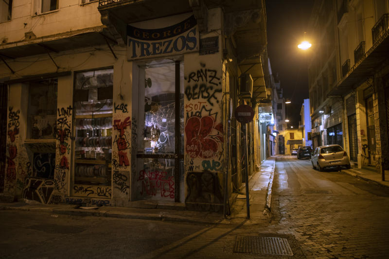In this Thursday, July 4, 2019 photo, a shop is covered with graffiti in Psiri district , central Athens. Some parts of central Athens are so afflicted with graffiti _ largely undecipherable squiggles in bold, broad strokes _ that few facades remain untouched and property owners give up on repainting. (AP Photo/Petros Giannakouris)