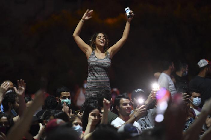 People celebrate in the street after Tunisian President Kais Saied announced the dissolution of parliament and Prime Minister Hichem Mechichi's government in Tunis on July 25 (AFP via Getty Images)