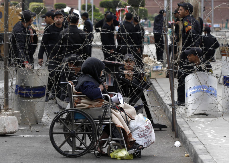 A woman in a wheelchair is sits next to a barbed wired fence securing the area around the presidential palace in Cairo, Egypt, Friday, Dec. 14, 2012. Opposing sides in Egypt's political crisis were staging rival rallies on Friday, the final day before voting starts on a contentious draft constitution that has plunged the country into turmoil and deeply divided the nation.(AP Photo/Petr David Josek)