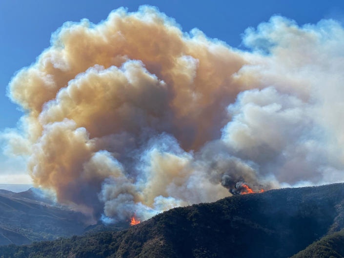 In this photo provided by Santa Barbara County Fire Department, the Alisal Fire continues to burn the dry vegetation in Refugio Canyon on Tuesday morning, Oct. 12, 2021, in Santa Barbara County, Calif. (Mike Eliason/Santa Barbara County Fire via AP)