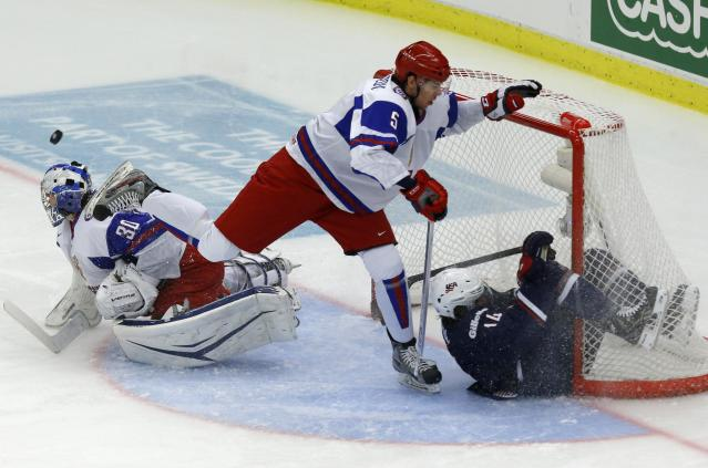 Russia's goalie Andrei Vasilevski (L) and Alexei Bereglazov make a save on Thomas Dipauli (R) falls down during the first period of their quarter-final game at the IIHF World Junior Championship ice hockey game in Malmo, Sweden, January 2, 2014. REUTERS/Alexander Demianchuk (SWEDEN - Tags: SPORT ICE HOCKEY)