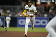 San Diego Padres shortstop Fernando Tatis Jr. gets ready to toss the ball to first for the out on Milwaukee Brewers' Travis Shaw during the sixth inning of a baseball game, Monday, April 19, 2021, in San Diego. (AP Photo/Gregory Bull)