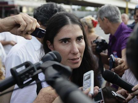 Cuba's best-known dissident, blogger Yoani Sanchez, speaks to reporters outside Havana's Jose Marti International Airport