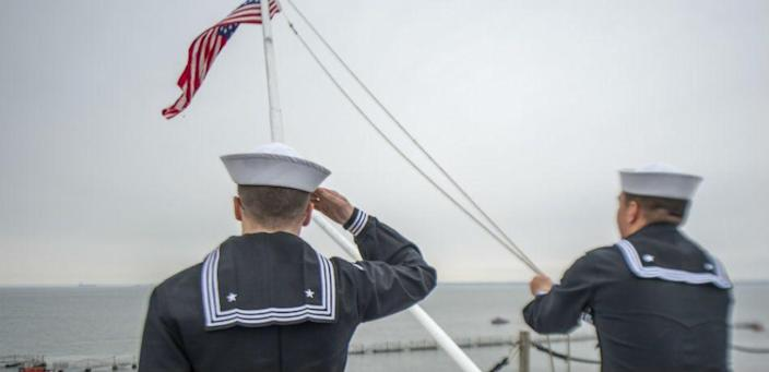 A sailor aboard the USS George HW Bush salutes the U.S. flag as another lowers it to half mast to honor the vessel's namesake after his death on December 1, 2018.
