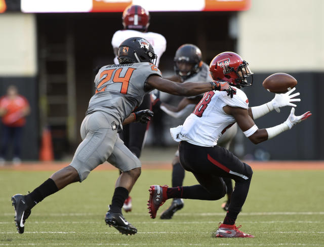 Texas Tech wide receiver Ja'Deion High, right, catches a pass under pressure from Oklahoma State's Jarrick Bernard during the first half of an NCAA college football game in Stillwater, Okla., Saturday, Sept. 22, 2018. (AP Photo/Brody Schmidt)
