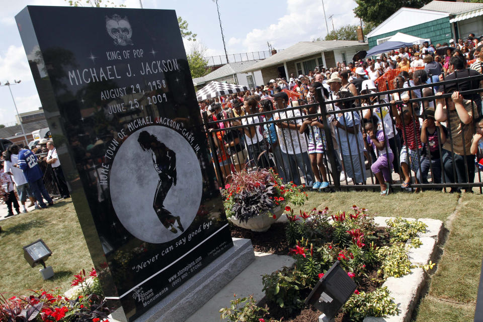 FILE - In this June 25, 2010 file photo, Michael Jackson fans gather around a monument that was unveiled in Gary, Ind., on the first anniversary of the pop icon's death. As the 10th anniversary of Jackson's death approaches, experts say his music legacy is still going strong despite the documentary's detailed abuse allegations. (AP Photo/John Smierciak, File)