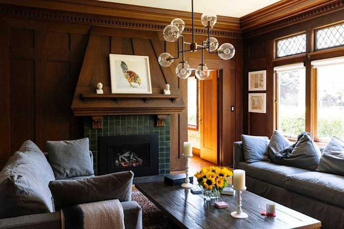 A RH chandelier crows the cozy den, where sofas are by Crate & Barrel. The artwork is a photograph by Patrice Casanova.