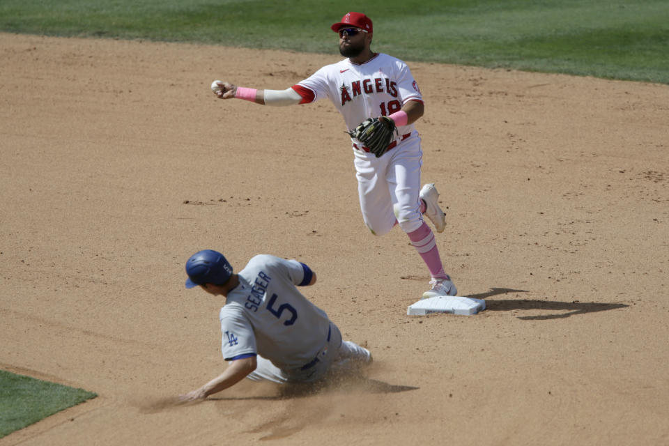Los Angeles Angels second baseman Jose Rojas throws to first over Los Angeles Dodgers' Corey Seager for a double play on Will Smith during the seventh inning of a baseball game in Anaheim, Calif., Sunday, May 9, 2021. (AP Photo/Alex Gallardo)