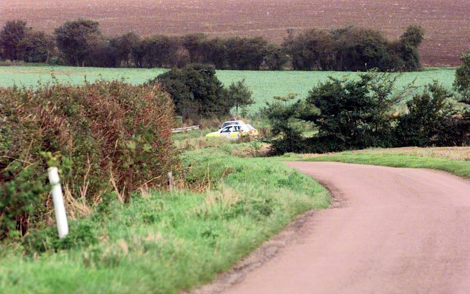 Police officers patrol the area where Hall's body was discovered in 1999 - PA