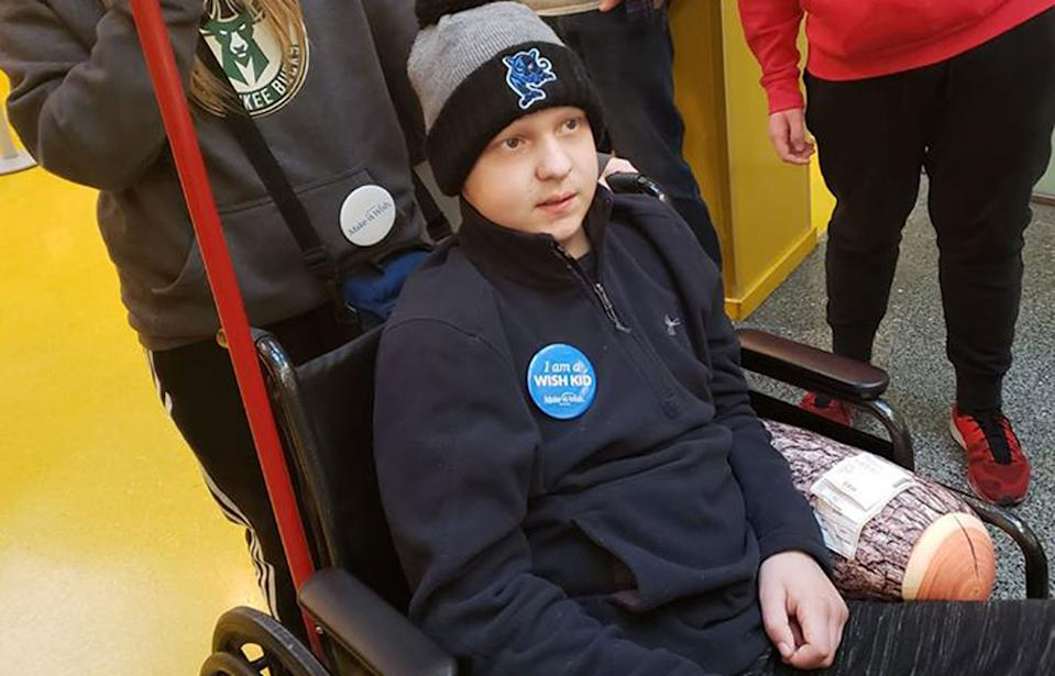 Michael Choroszy, 11, pictured in a wheelchair wearing a Make-A-Wish badge.