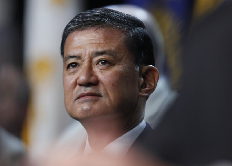 In this photo taken Aug. 2, 2010, Veterans Affairs Secretary Eric Shinseki listens to President Barack Obama speak about Iraq and Afghanistan at the Disabled American Veterans national convention in Atlanta. Although the number of veterans' disability claims keep soaring, Shinseki said Sunday, March 24, 2013, that he's committed to ending the backlog by 2015 by replacing paper with electronic records. About 600,000 claims, or 70 percent, are considered backlogged, and the number of claims pending for more than 125 days has nearly quadrupled under Shinseki's watch. (AP Photo/Charles Dharapak)
