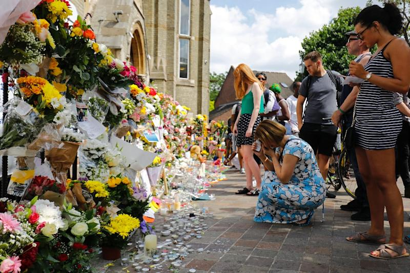 People look at floral tributes for victims of the Grenfell Tower block fire that have been left outside the Notting Hill Methodist Church in west London, on June 17, 2017 (AFP Photo/Tolga AKMEN)
