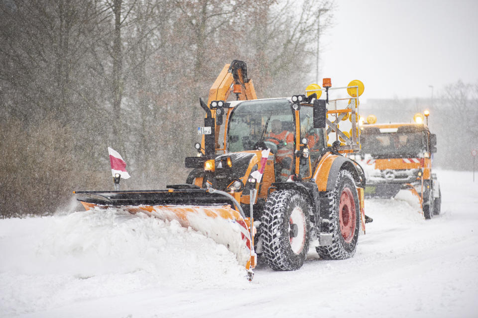 Clearing vehicles push piles of snow off a road in Bielefeld, Germany, Sunday, Feb. 7, 2021. (Marcel Kusch/dpa via AP)