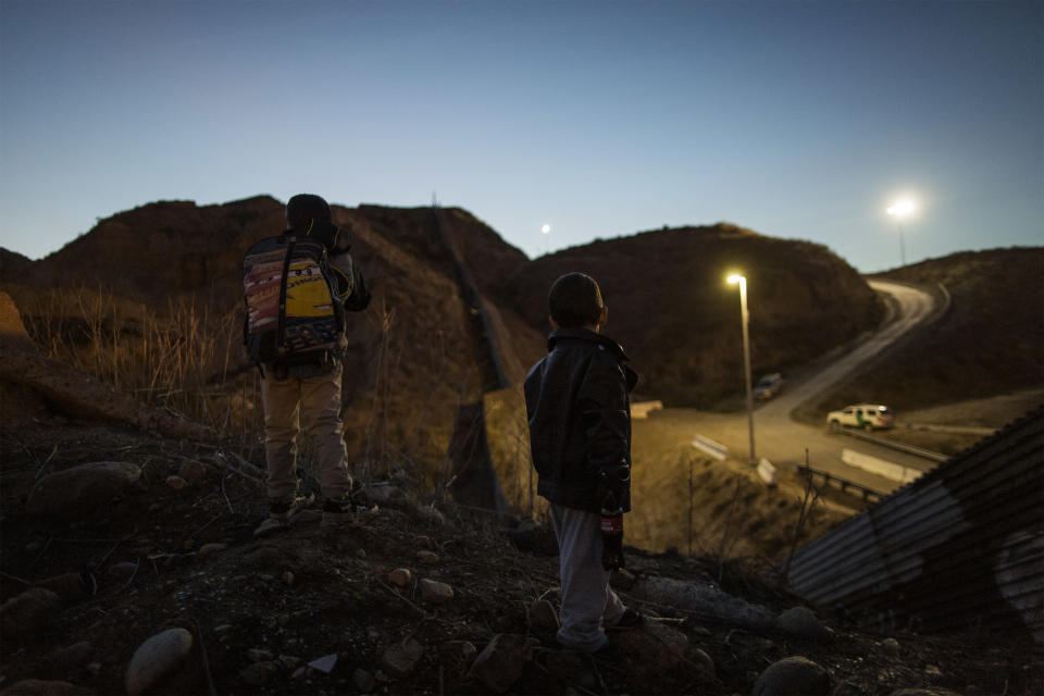 Oliver (7) and Schneider (4) watch the border wall between Mexico and US on December 1, 2018. (Photo: Fabio Bucciarelli for Yahoo News)