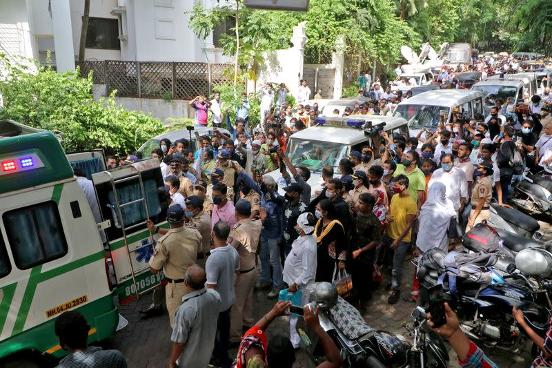 Fans use their mobile phones to take pictures of an ambulance carrying the body of Bollywood actor Dilip Kumar for his funeral in Mumbai