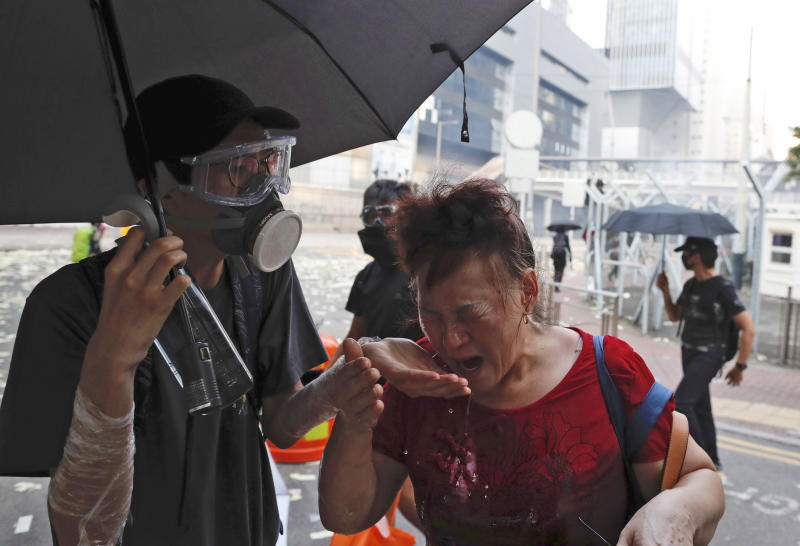 A black-clad protestor splashes water on the face of a woman after police fired tear gas shells in Hong Kong, Oct. 1, 2019. (Photo: Gemunu Amarasinghe/AP)