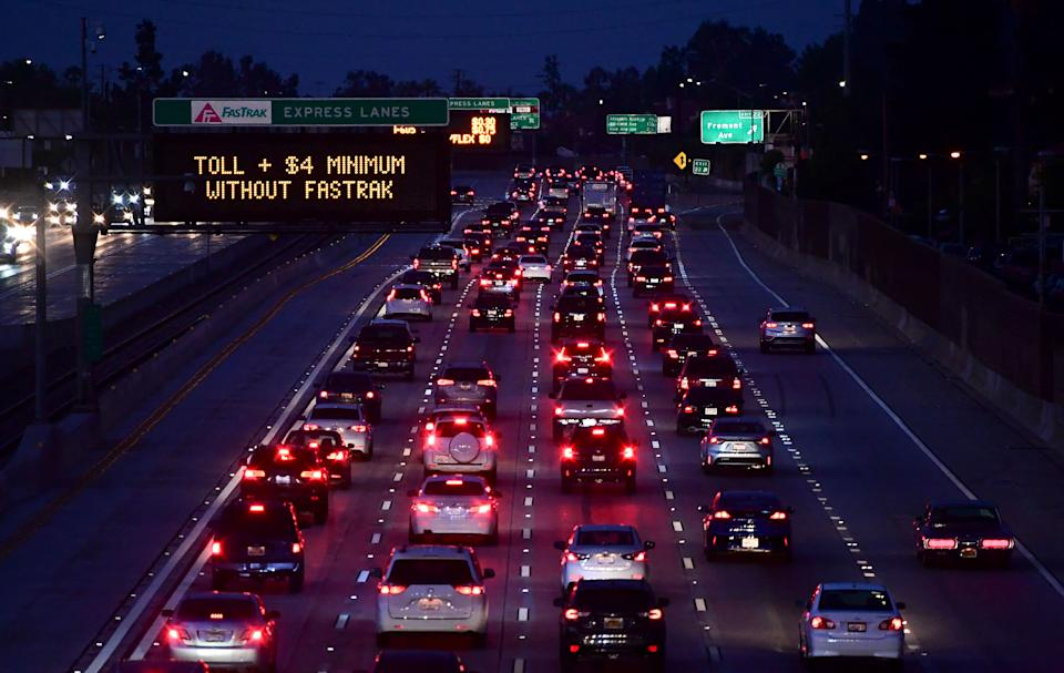 Brakelights come on as vehicles head east out of Los Angeles on the Interstate 10 freeway in Alhambra, California on May 27, 2021, ahead of the Memorial Day weekend. (Photo by Frederic J. BROWN / AFP)