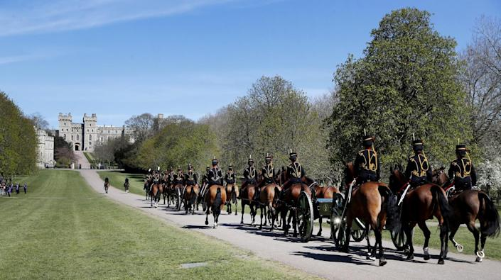 The King's Troop Royal Horse Artillery rides on a road toward Windsor Castle past trees and grass.