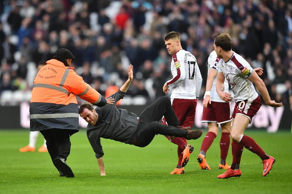 Burnley's Ashley Barnes (R) trips up a pitch invader after furious West Ham fans ran riot at The London Stadium on March 10, 2017 (AFP Photo/Ben STANSALL)