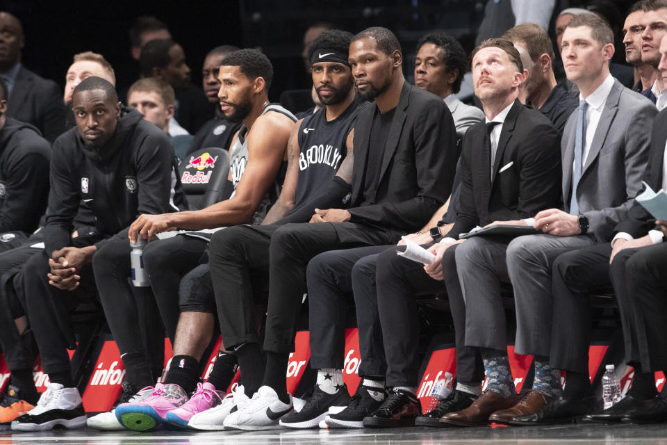 Brooklyn Nets guard Kyrie Irving, center left, and forward Kevin Durant, center right, watch the action from the bench during the second half of an NBA basketball game against the New Orleans Pelicans, Monday, Nov. 4, 2019, in New York. (AP Photo/Mary Altaffer)