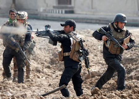 An Iraqi special forces soldier fires as other soldiers runs across a street during a battle in Mosul