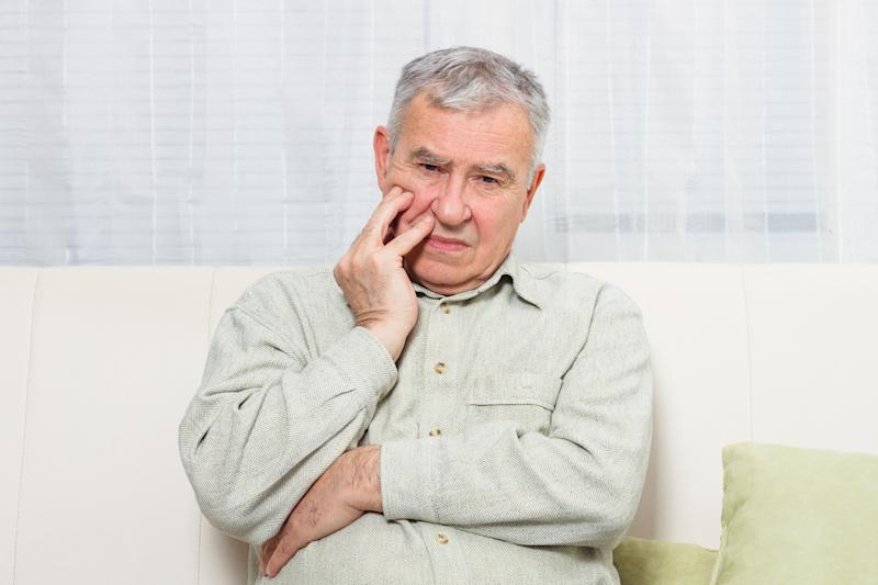 Older man with concerned expression sitting on couch while holding face in hand.