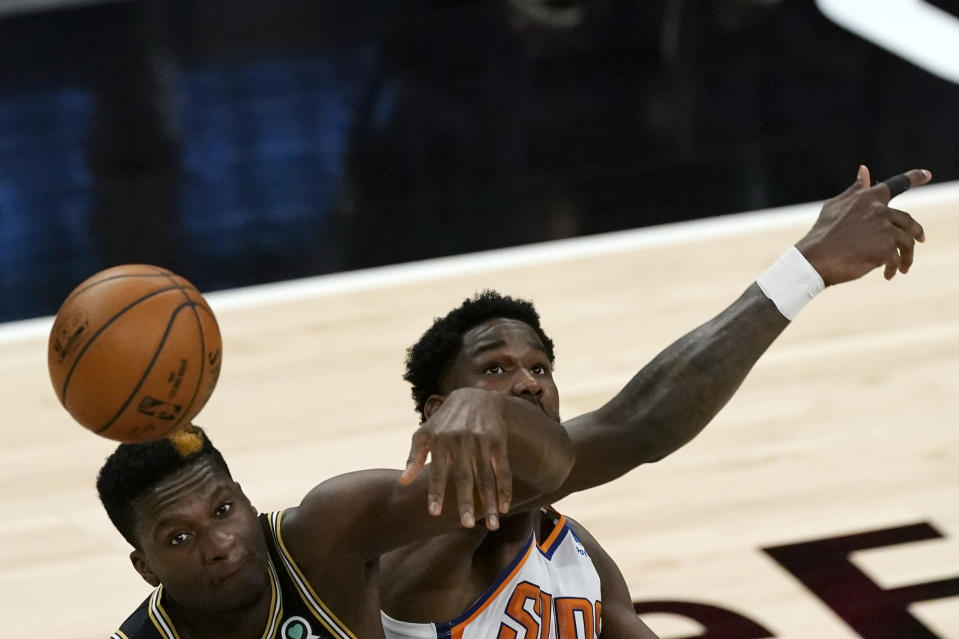 Atlanta Hawks center Clint Capela (15) and Phoenix Suns center Deandre Ayton (22) battle for the opening tip in the first half of an NBA basketball game Wednesday, May 5, 2021, in Atlanta. (AP Photo/John Bazemore)