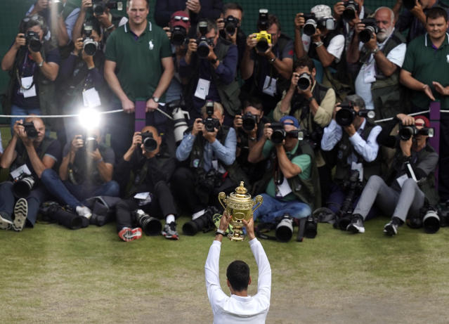 Serbia's Novak Djokovic holds up the winners trophy after defeating Switzerland's Roger Federer during the men's singles final match of the Wimbledon Tennis Championships in London, Sunday, July 14, 2019. (Will Oliver/Pool Photo via AP)