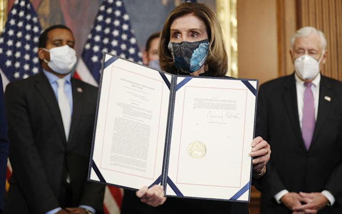 Speaker of the House Nancy Pelosi holds the signed Article of Impeachment against US President Donald J. Trump during an engrossment ceremony - SHAWN THEW/EPA-EFE/Shutterstock/Shutterstock