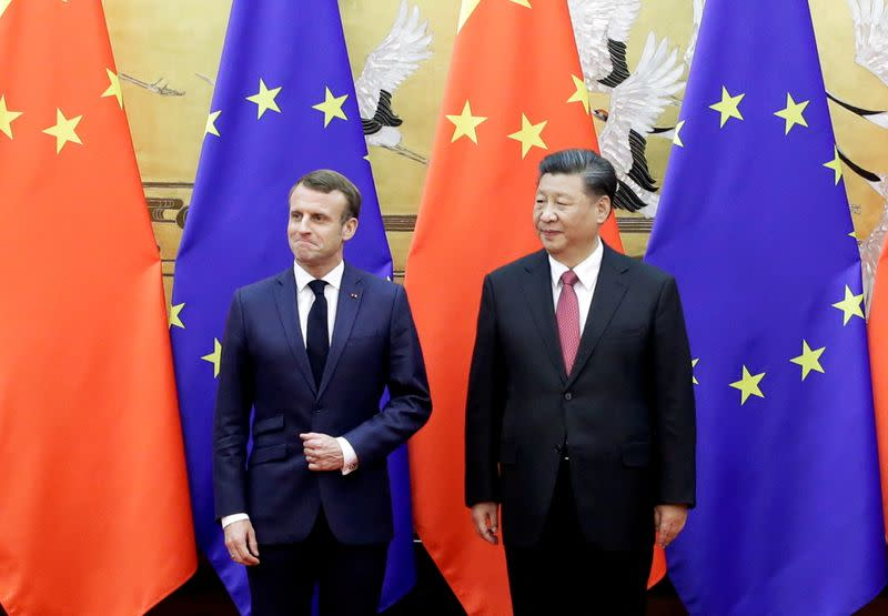 FILE PHOTO: Chinese President Xi Jinping and French President Emmanuel Macron stand in front of Chinese and EU flags at a signing ceremony inside the Great Hall of the People in Beijing