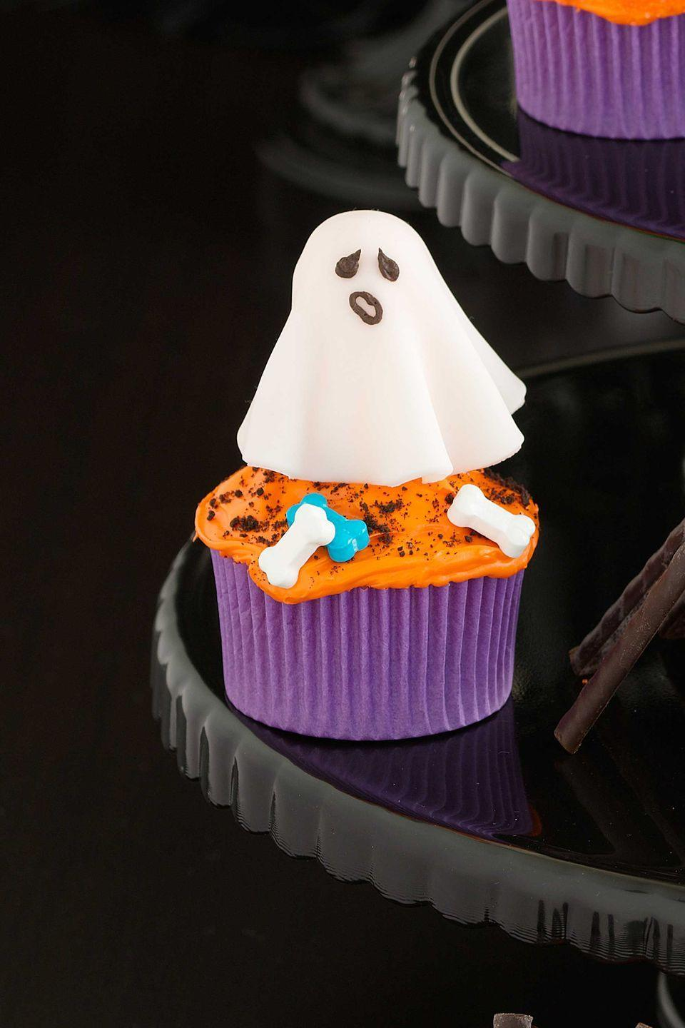 """<p>This friendly ghost is simple to make and easier to enjoy! The fondant ghost is draped over a circus peanut candy, and floats over an orange cupcake with crushed cookies and bone-shaped candies.</p><p><a href=""""https://www.womansday.com/food-recipes/food-drinks/recipes/a10762/ghost-cupcakes-122191/"""" rel=""""nofollow noopener"""" target=""""_blank"""" data-ylk=""""slk:Get the Ghost Cupcakes recipe."""" class=""""link rapid-noclick-resp""""><em>Get the Ghost Cupcakes recipe.</em></a></p>"""
