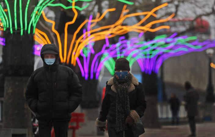 A couple wear face coverings as they stroll past illuminated trees on the Southbank in London, Friday, Jan. 8, 2021. Britain's Prime Minister Boris Johnson has ordered a new national lockdown for England which means people will only be able to leave their homes for limited reasons, with measures expected to stay in place until mid-February. (AP Photo/Frank Augstein)