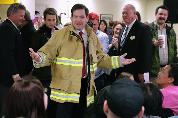 <p>Marco Rubio, R-Fla., tries on a firefighter jacket made for him at Globe Manufacturing during a campaign town hall event with employees, Feb. 3, 2016, in Pittsfield, N.H. Rubio is hoping to gather momentum in New Hampshire after placing third in Monday's Iowa caucuses, finishing one percentage point behind Donald Trump and four behind the winner, Sen. Ted Cruz, R-Texas. <i>(Photo: Chip Somodevilla/Getty Images)</i></p>
