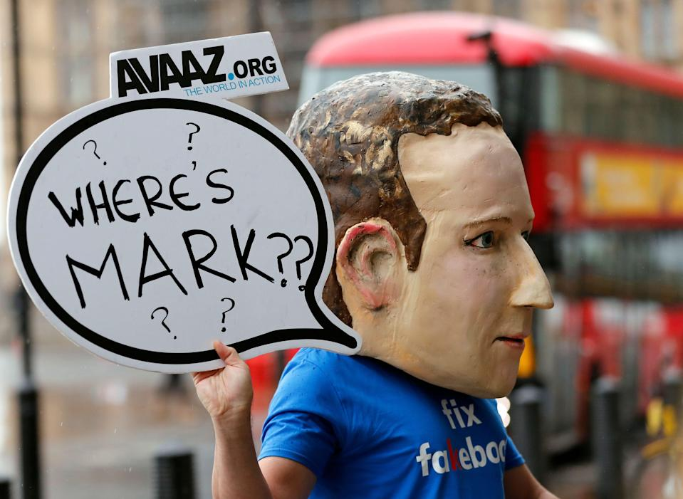 An activist wearing a Facebook CEO Mark Zuckerberg mask stands in front of Portcullis House in Westminster as an international committee of parliamentarians met for a hearing on the impact of disinformation on democracy in London, Tuesday, Nov. 27, 2018. (AP Photo/Frank Augstein)