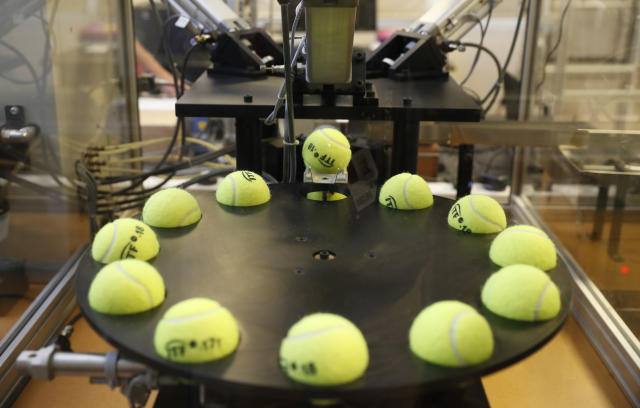 In this photo taken Friday June, 28, 2019, a tennis balls are lined up to squashed by pistons as they are tested by the International Tennis Federation (ITF) lab in Roehampton, near Wimbledon south west London. Based for about 20 years in a three-room area on what used to be a pair of squash courts in Roehampton, the ITF tech lab is filled with more than $1 million worth of machines that help make sure rules are followed and parameters are met. (AP Photo/Alastair Grant)