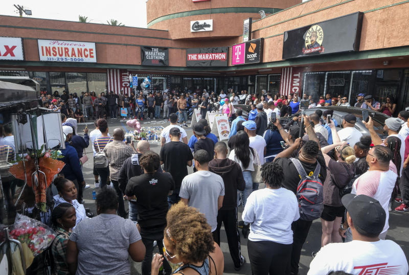 Fans of rapper Nipsey Hussle gather at a makeshift memorial in the parking lot of the Marathon Clothing store in Los Angeles, Monday, April 1, 2019. Hussle was killed in a shooting outside his clothing store on Sunday. (AP Photo/Ringo H.W. Chiu)