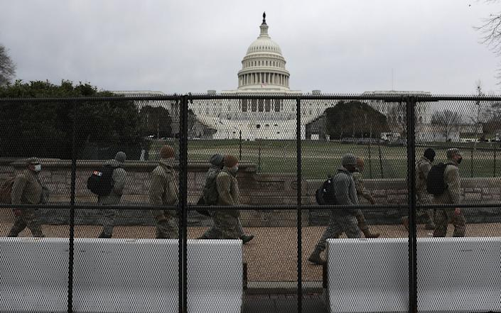 Members of the DC National Guard walk behind a fence placed around the US Capitol building - Getty