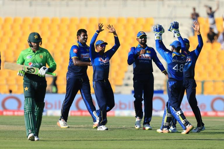 Pakistan's Shoaib Malik (L) leaves the field after being dismissed by Sri Lanka's Nickwella Dickwella during their second one day international (ODI) match at Sheikh Zayed Stadium in Abu Dhabi on October 16, 2017