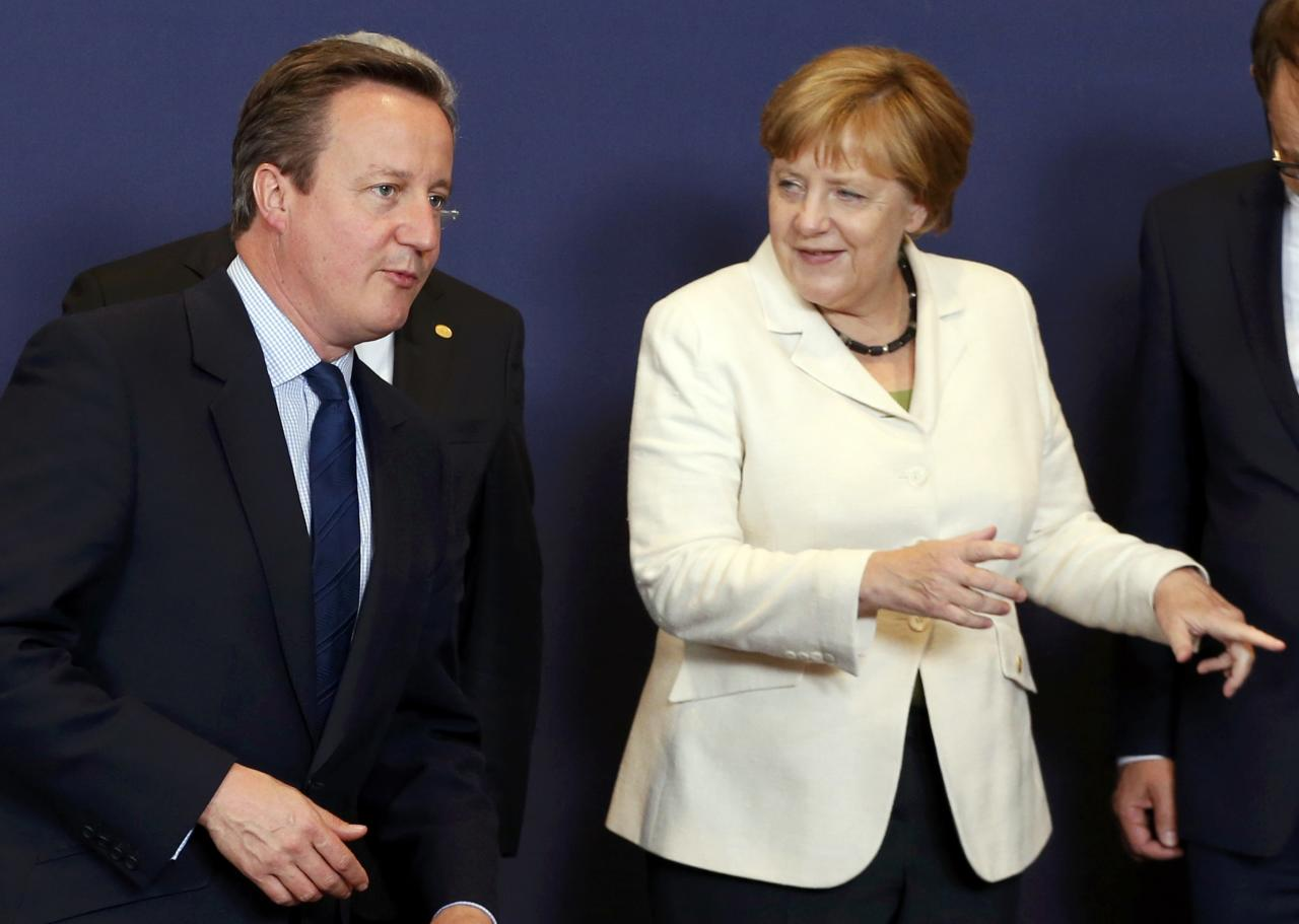 British Prime Minister David Cameron (L) and German Chancellor Angela Merkel take their places for the traditional family photo at he EU summit in Brussels, Belgium, June 28, 2016.    REUTERS/Francois Lenoir/File Photo