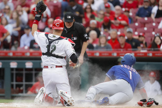 Texas Rangers' Elvis Andrus (1) scores against Cincinnati Reds catcher Curt Casali (12) in the first inning of a baseball game, Friday, June 14, 2019, in Cincinnati. (AP Photo/John Minchillo)