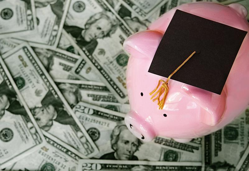 Piggy bank with graduation cap on pile of money