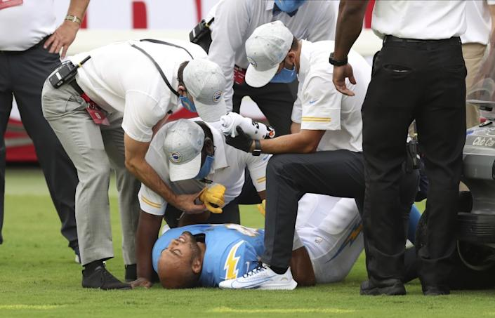 """Chargers running back Austin Ekeler is attended to after suffering a hamstring injury against the Tampa Bay Buccaneers on Sunday. He is projected to be sidelined at least a month. <span class=""""copyright"""">(Mark LoMoglio / Associated Press)</span>"""