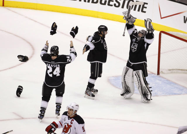 Los Angeles Kings defenseman Drew Doughty (8), Los Angeles Kings center Colin Fraser (24) and Los Angeles Kings goalie Jonathan Quick (32) celebrate as time runs off the clock to beat the New Jersey Devils 6-1 during Game 6 of the NHL hockey Stanley Cup finals,Monday, June 11, 2012, in Los Angeles. (AP Photo/Jae C. Hong)