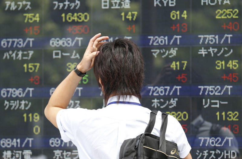 A man looks at an electronic stock board of a securities firm in Tokyo, Monday, Sept. 9, 2013. Asian stocks opened higher on Monday, lifted by Tokyo's Olympic bid victory, Chinese export growth and an Australian conservative coalition's election victory. Japanese stocks rallied, with the Nikkei 225 jumping nearly 1.9 percent to 14,122.10, and the yen fell after Tokyo was chosen to host the 2020 Summer Olympics and a revised estimate showed the economy grew faster than previously reported in the second quarter.(AP Photo/Koji Sasahara)