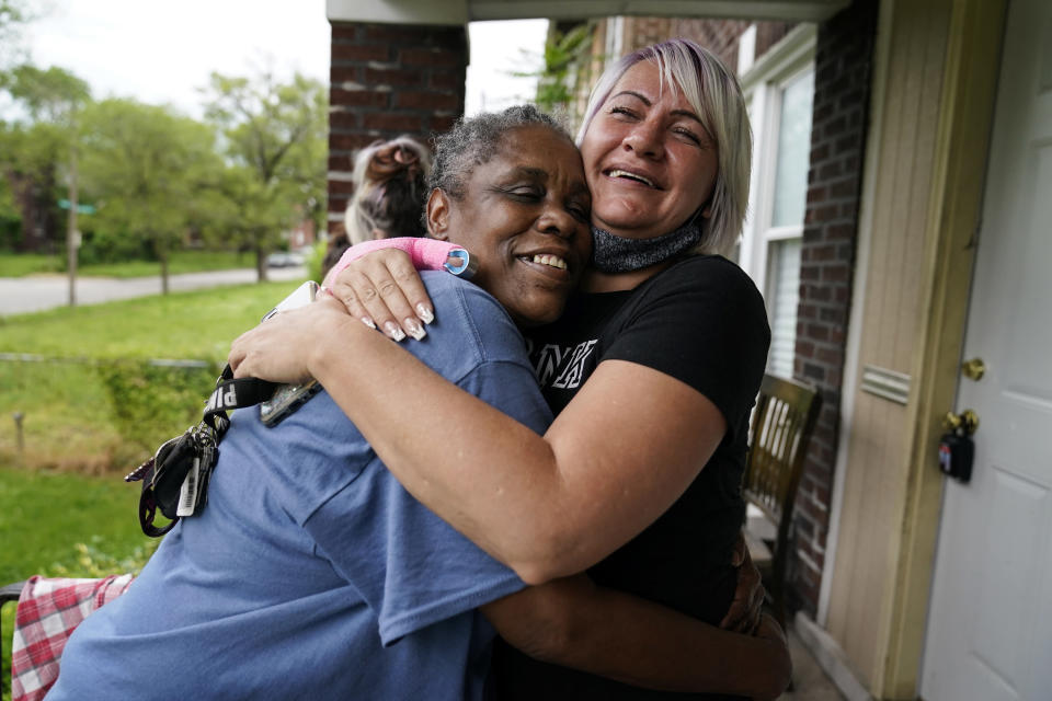 Lynda Brooks, left, hugs Amy Ford in St. Louis on Wednesday, May 19, 2021. Brooks has been in recovery now for several months, and she prays for God to remain scared of the drugs. She got a job and an apartment, and proudly keeps her new keys dangling from a shoelace around her neck. Her family told her they are proud of her. She said that feels like heaven. (AP Photo/Brynn Anderson)